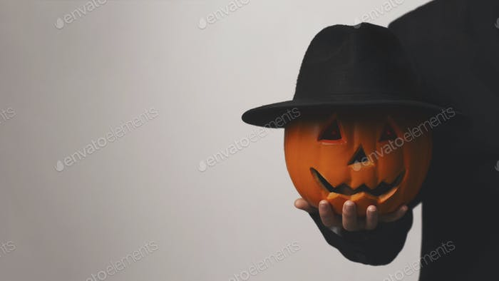 Jack o Lantern holding his pumpkin head with hat in hand