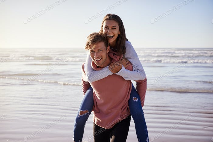 Man Giving Woman Piggyback On Winter Beach Vacation