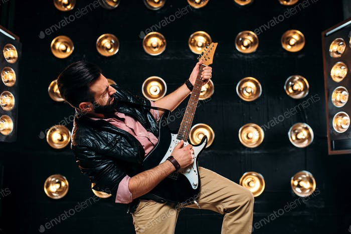 Male guitarist on stage with decorations of lights