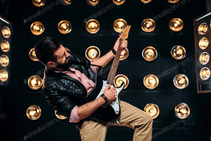 Männlicher Gitarrist auf der Bühne mit Dekorationen von Lichtern