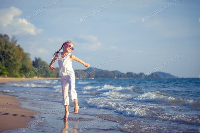 Little girl  dancing on the beach at the day time.