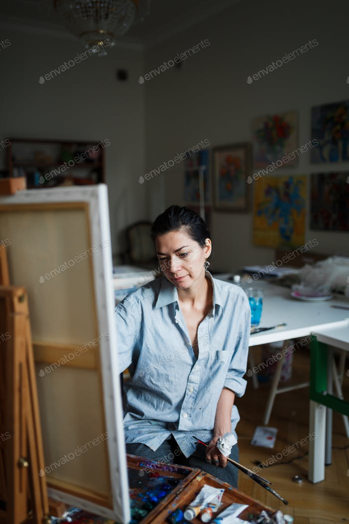 A young woman artist paints an oil painting on the easel.