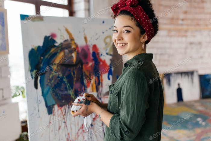 Young pretty smiling woman with dark curly hair drawing picture
