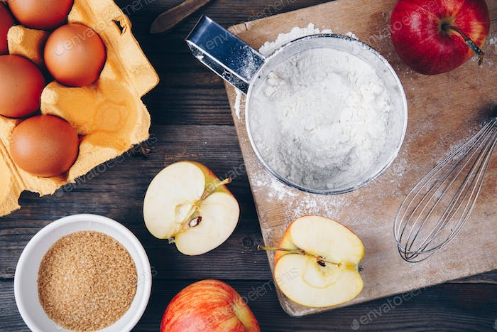 Ingredients for apple pie cooking with fresh red apples, flour, eggs, brown sugar and spices
