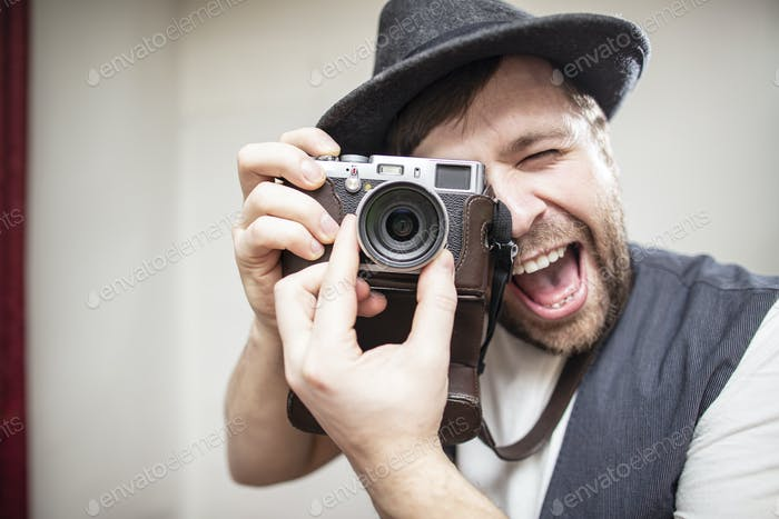 Positive photographer in a felt hat takes a picture on the camera