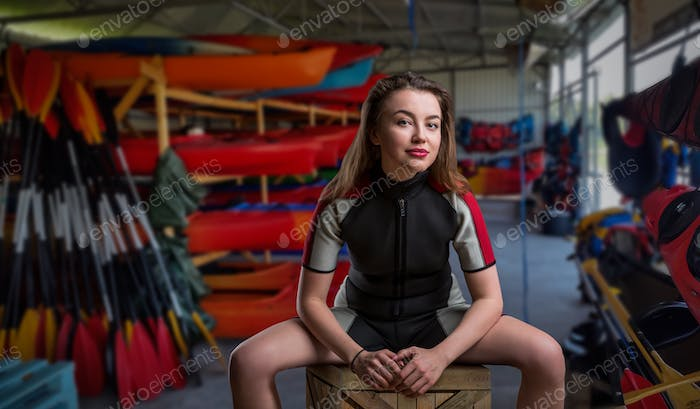 Female sportman in wetsuit, boats on background