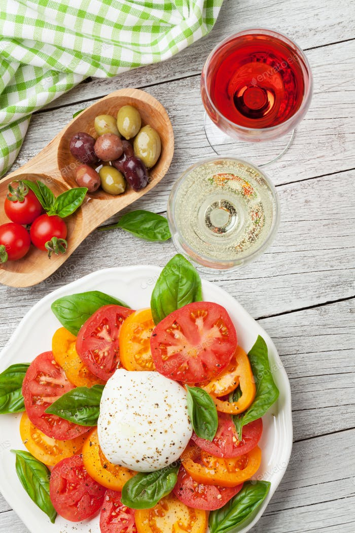 Caprese salad with tomatoes, basil and mozzarella with wine