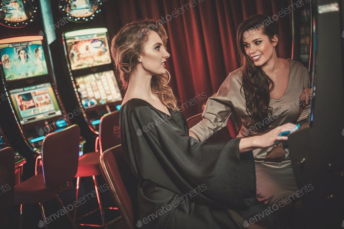 Beautiful women near slots machines in a luxury casino interior