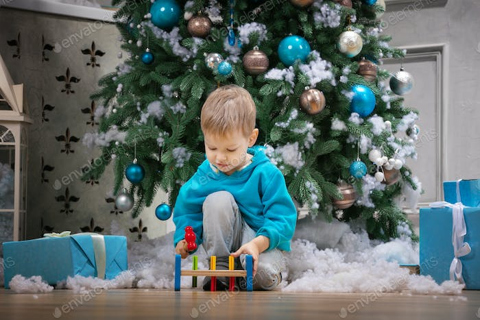 Preschool boy playing with wooden hammer toy while sitting beside Christmas tree