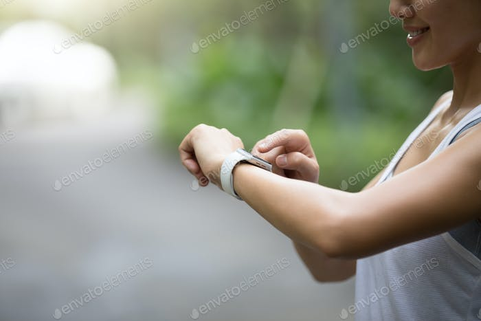 Woman runner looking at her smartwatch on park trail