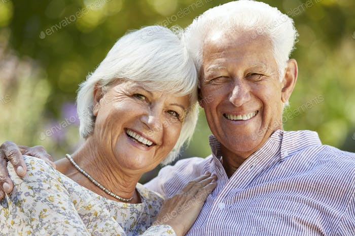 Happy senior couple embracing in garden, head and shoulders
