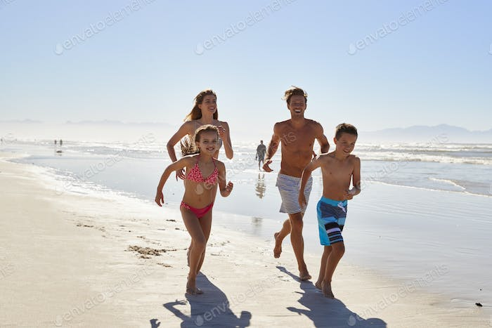 Family On Summer Vacation Running Along Beach Together