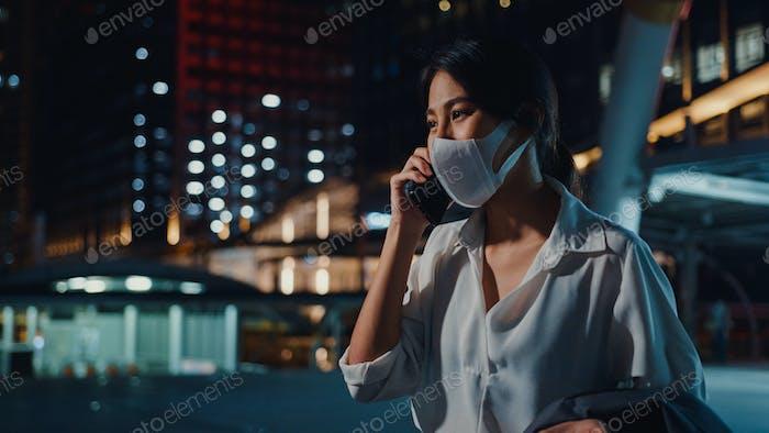 Asia businesswoman wear medical face mask talk via phone while walk alone.
