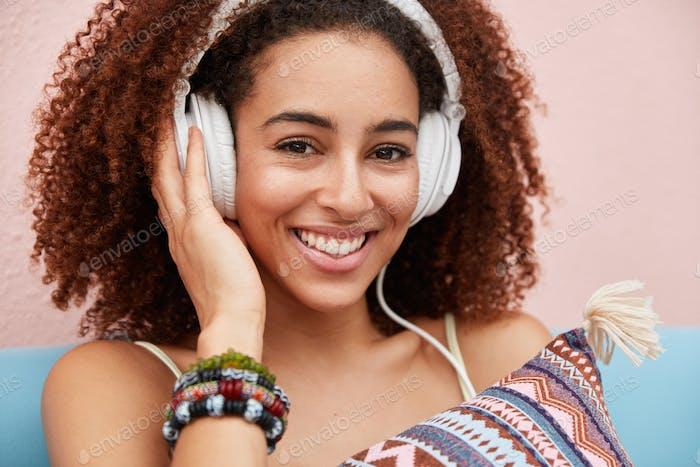 Close up shot of pleasant looking dark skinned African American female listens audio book in headpho