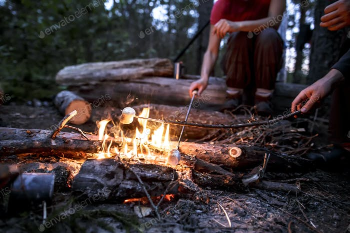 Two people are frying marshmeloo on a summer camp