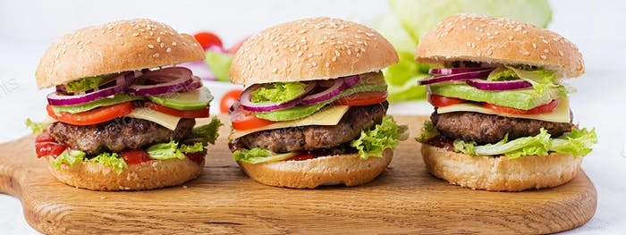 Big sandwich - hamburger burger with beef, avocado, tomato and red onions on light background