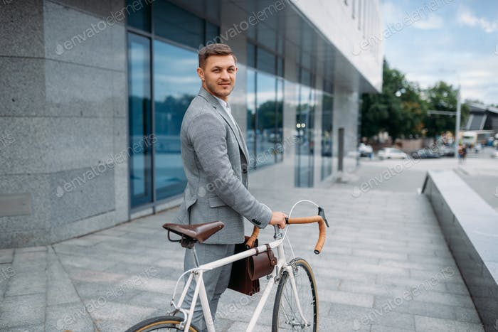 One businessman with briefcase cycling in downtown