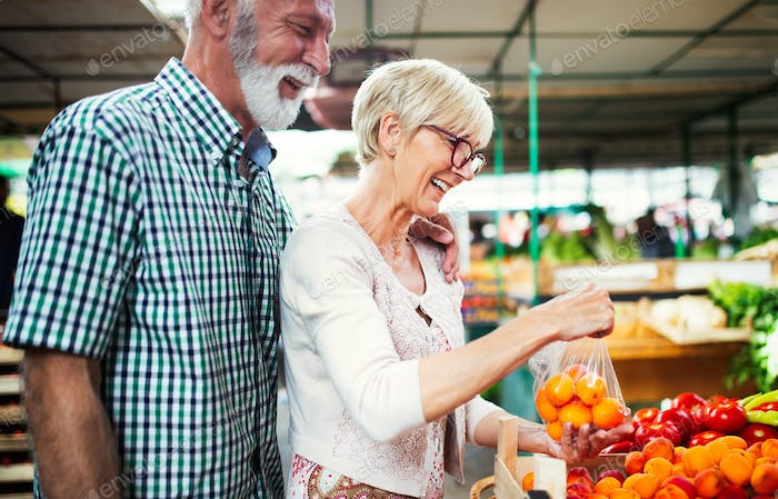 Picture of senior couple at marketplace buying vegetables