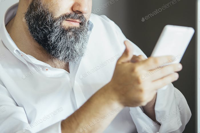 Close-up of man typing on cell