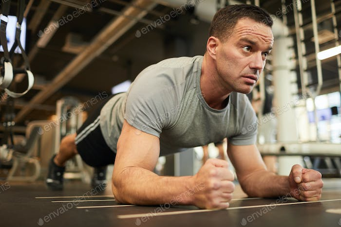 Muscular Man Doing Plank Exercise in Gym