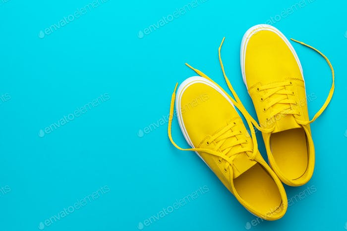 Top View Of Yellow Untied Sneakers On Blue Turquoise Background With Copy Space