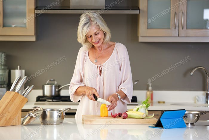 happy older woman in kitchen cutting vegetables
