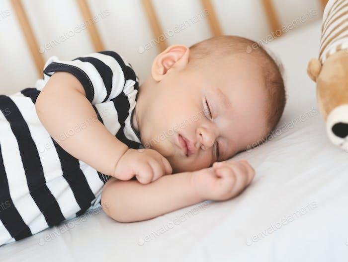 Sleeping newborn baby lying on his side in crib, closeup