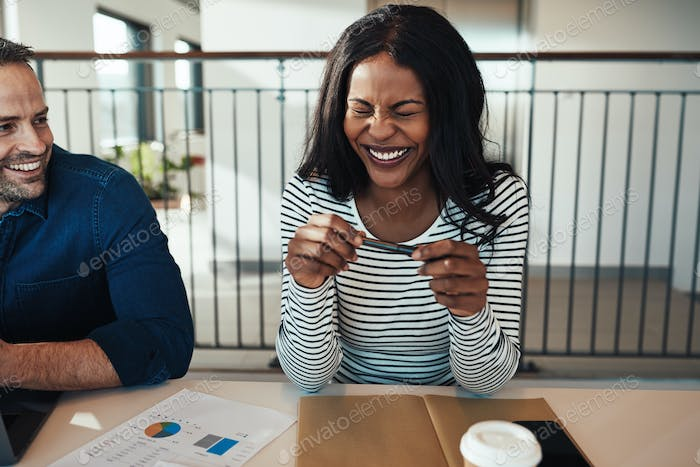 Laughing young businesswoman sitting with a colleague in an office