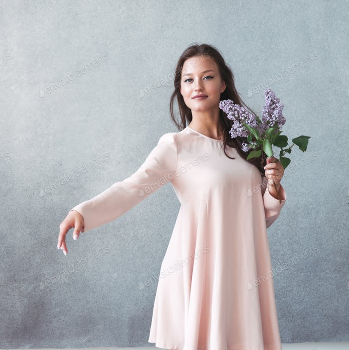 Woman with lilac brunch over gray background