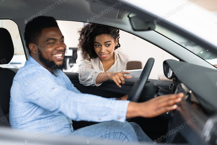 African Wife Helping Husband Choose New Car In Dealership Shop