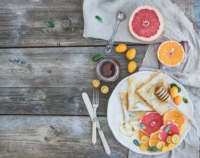 Spring vitamin breakfast set. Thin crepes or pancakes with fresh grapefruit, orange, kumquat