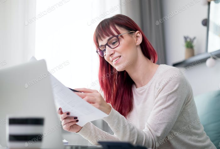 Happy woman at home using laptop and checking bills and invoice document