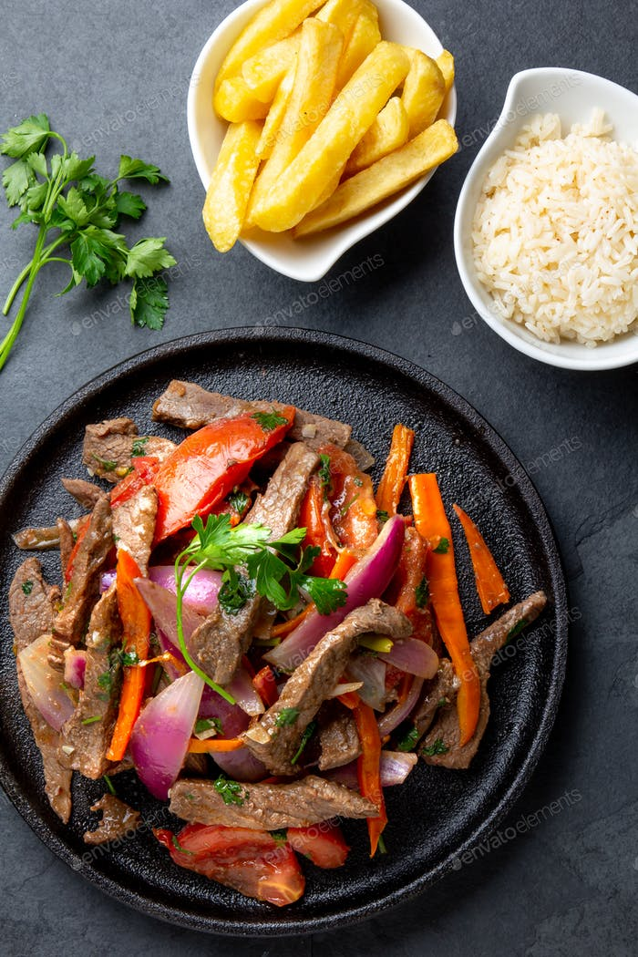 Peruvian dish Lomo saltado - beef tenderloin with purple onion, yellow chili, tomatoes