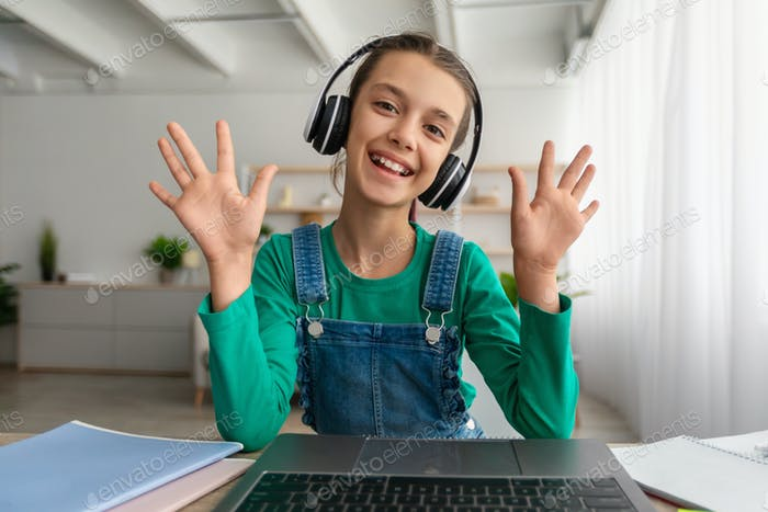 Girl sitting at desk, having video call wearing headphones