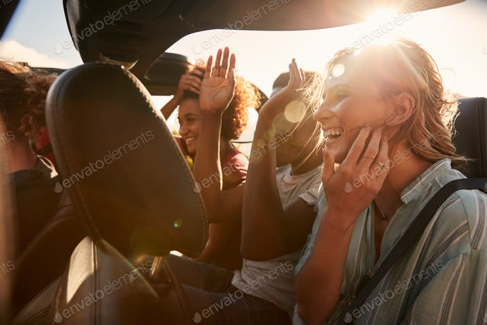 Happy young adult friends on a road trip vacation travelling in the back of an open car