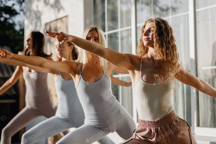 Four young women are practising yoga in the open air in the garden near the house in the sunny