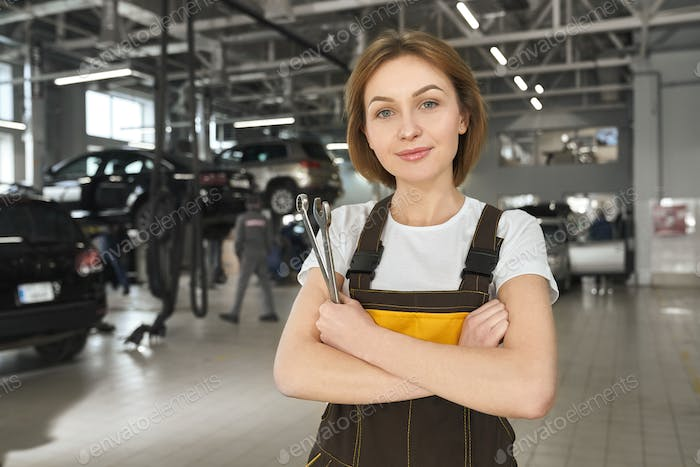 Female mechanic with wrenches posing in autoservice
