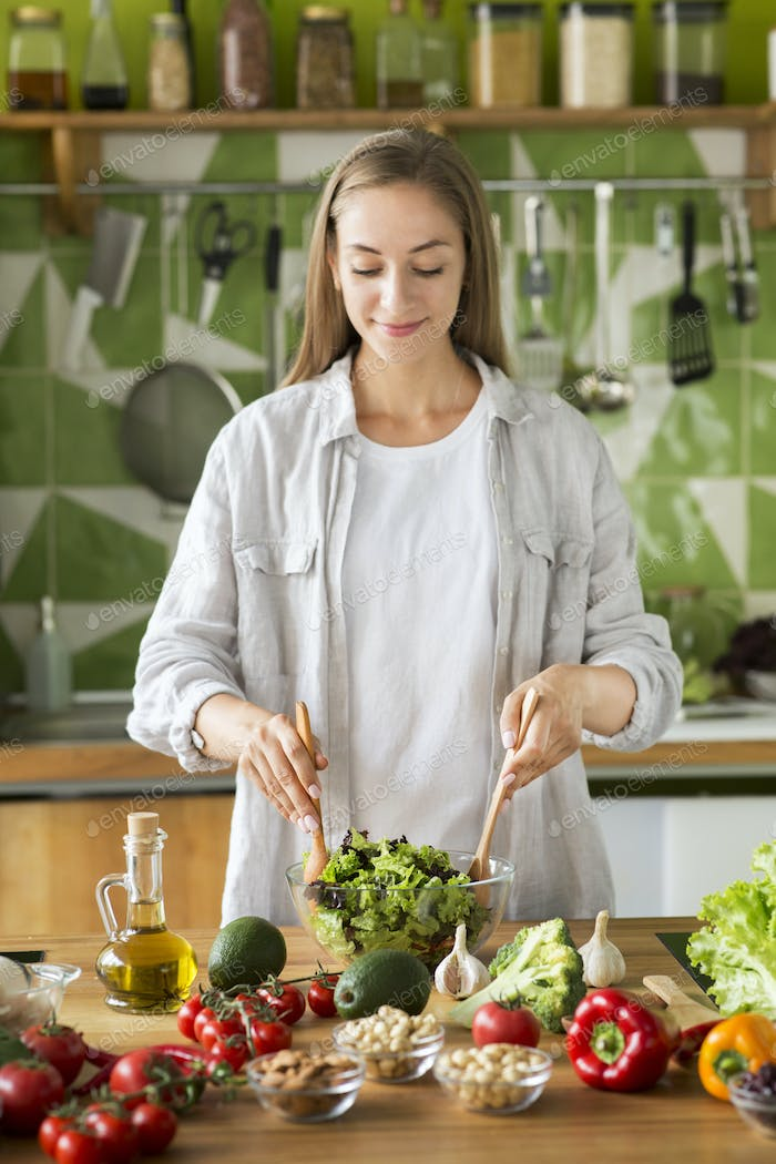 Only healthy food. Attractive young woman mixing salad