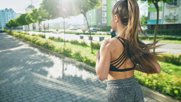 Unrecognizable woman running in morning streets
