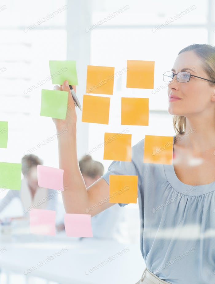 Concentrated female artist looking at colorful sticky notes at the office