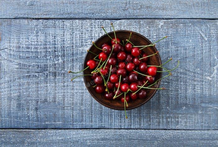 Sweet fresh cherries on blue wood background