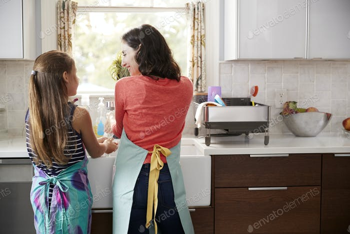 Mum and daughter washing hands at kitchen sink, back view