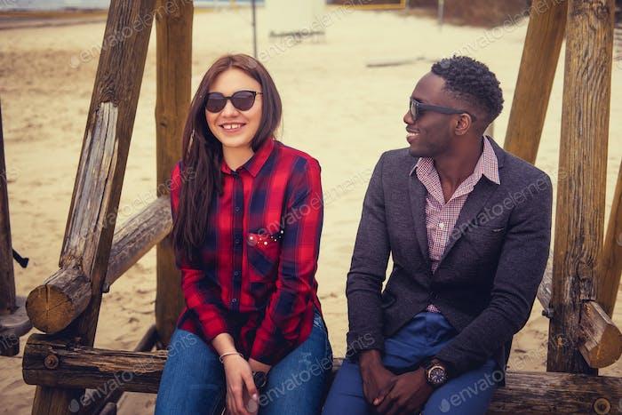 Афро-американский парень и кавказская женщина на пляже.
