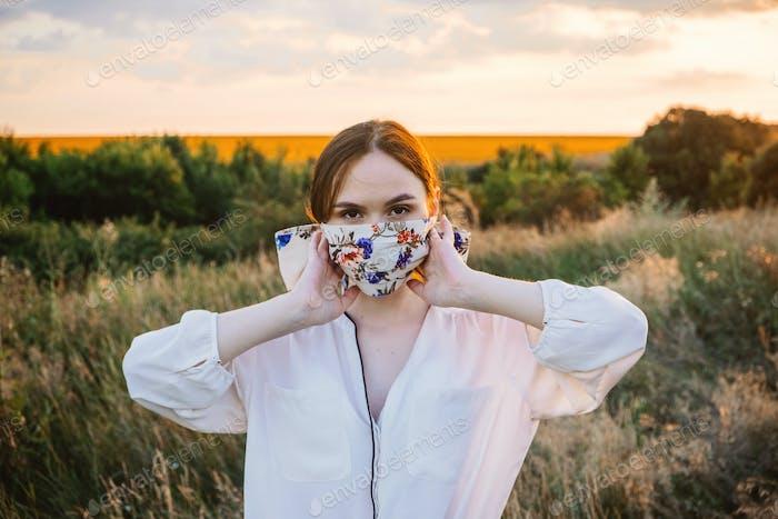 Máscaras de declaración, diseño de máscara de flores de bricolaje. Chica en máscara de cara decorada con flores