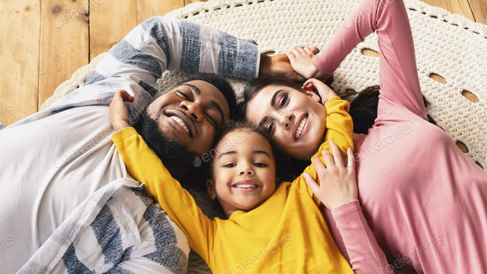 Family evening multiracial family. Daughter hugging parents