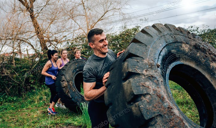 Participant in an obstacle course turning wheel