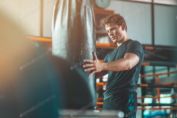Trennen Sie nie mit dem Fitnessstudio. Athletischer Mann steht in der Nähe eines Boxsacks im Fitnessstudio.