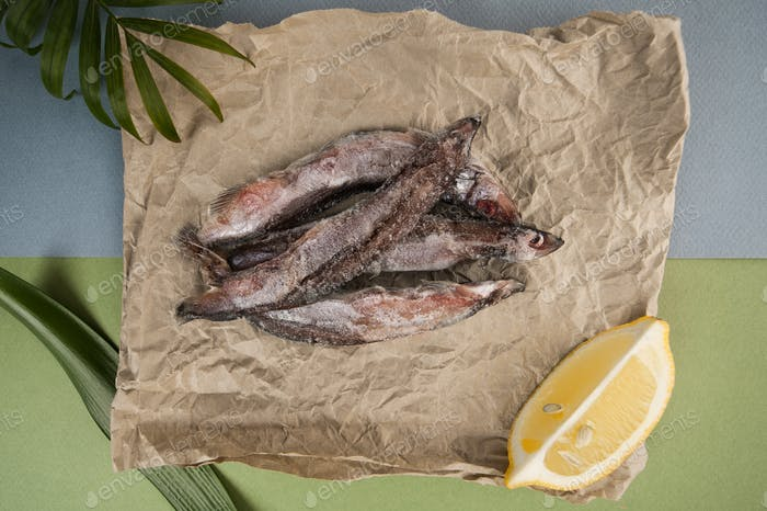 The raw frozen capelin rests on the kraft paper on a light blue-