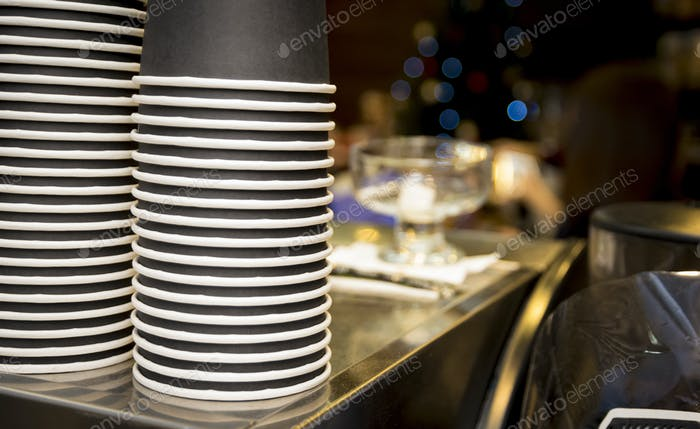 Stack of a paper cups on the top of a coffee machine
