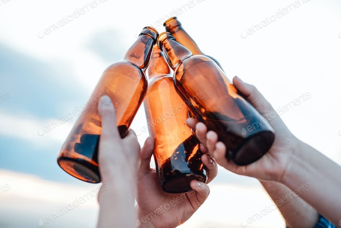 People are raising and clinking brown beer bottles